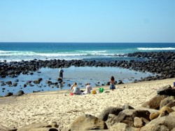Gold Coast Beach at Burleigh with rocks and sand for family fun.